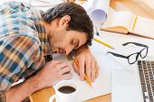 foto of sleeping  - Top view of young man sleeping while sitting at his working place