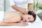 picture of ear candle  - Relaxed brunette getting an ear candling treatment at the spa - JPG
