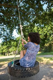 foto of tire swing  - Pretty young woman in tire swing on a summers day - JPG