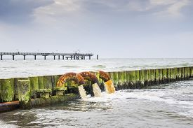 stock photo of polution  - Beach on the Baltic Sea with sewage pipes that pollute the sea - JPG
