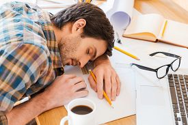 pic of adults only  - Top view of young man sleeping while sitting at his working place  - JPG