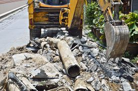 image of backhoe  - Backhoe Digging soil to replace new Asbestos cement pipe - JPG