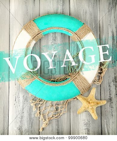 Voyage concept. Lifebuoy on wooden background