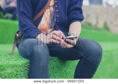 Woman Sitting On Astro Turf Using Smart Phone