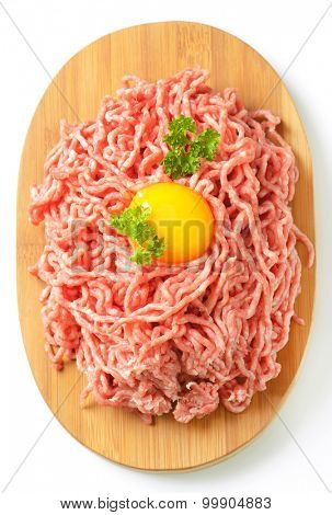 raw minced meat with egg yolk on oval wooden cutting board