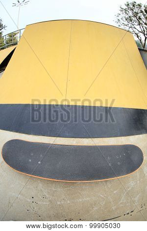 closeup of a skateboard and yellow ramp at skatepark