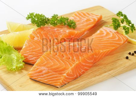 close up of raw salmon fillets with lemon and parsley on wooden cutting board