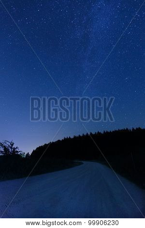 Empty Country Road Against Night Sky And Visible Milky Way