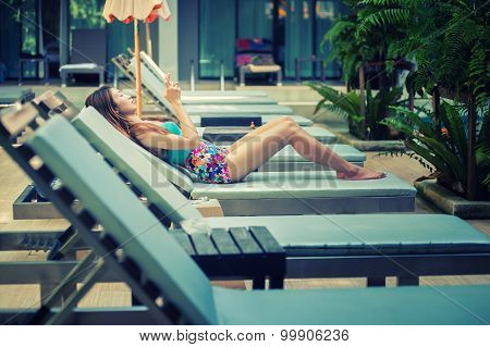 Beautiful Woman Using A Smart Phone On Lounger Near Swimming Poo