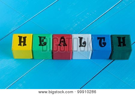 Health - word on children's colourful cubes or blocks. Colourful wooden background