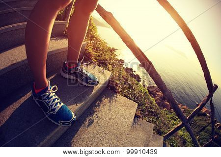 young woman runner legs on seaside mountain stairs