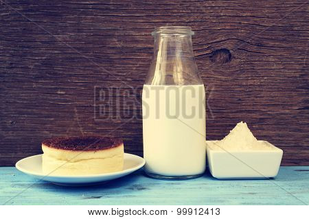 a cheesecake and some of the ingredients to prepare it, such as light cream or wheat flour, on a blue rustic wooden surface, with a filter effect