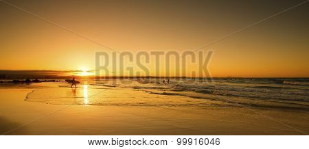 Single surfer walking into ocean water with surfboard at sunset