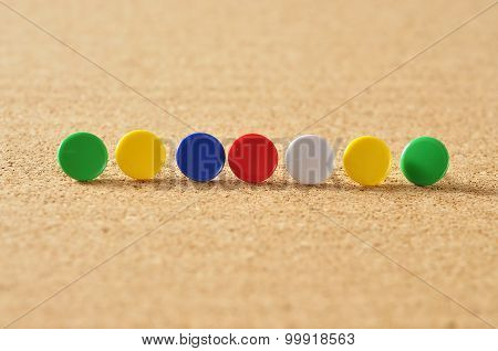 Close Up of Colorful Push Pins On Board