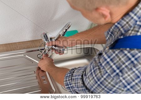 Plumber Fixing Faucet In Kitchen Sink