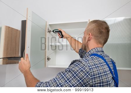 Carpenter Drilling In Cabinet