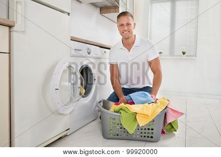 Man Putting Colorful Towels Into The Washing Machine