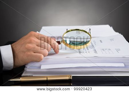 Businessperson Hands Analyzing Receipt With Magnifying Glass