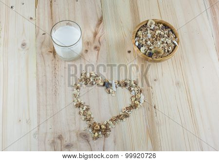 Heart-shaped muesli bowl of muesli and glass of milk on the wooden table.