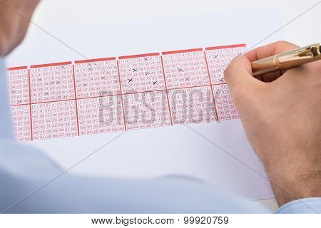 Businessperson Marking On Lottery Ticket