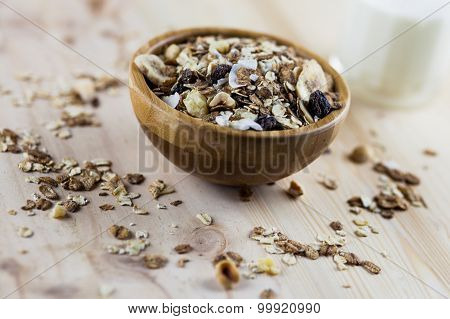 Muesli granola and milk in blurred wooden background. (Shallow aperture intended for the aesthetic q
