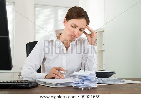 Contemplated Businesswoman Calculating Receipts