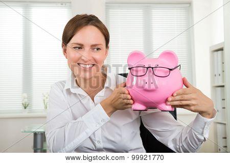 Businesswoman With Piggybank At Desk