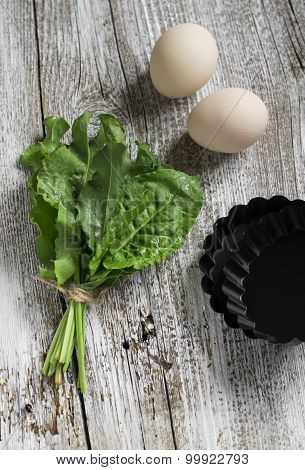 Fresh Sorrel, Eggs And Baking Dish On A Light Wooden Background, Ingredients For Baked Eggs With Sor