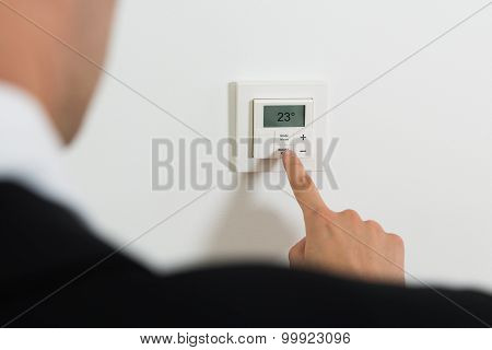 Businessperson Setting Temperature On Digital Thermostat