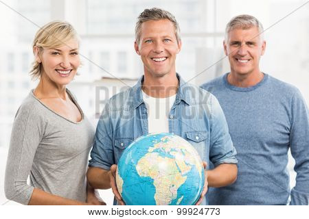 Portrait of a smiling businessman holding terrestrial globe at office
