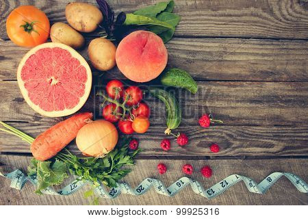 Fruits, vegetables and in measure tape in diet on wooden background . Toned image.