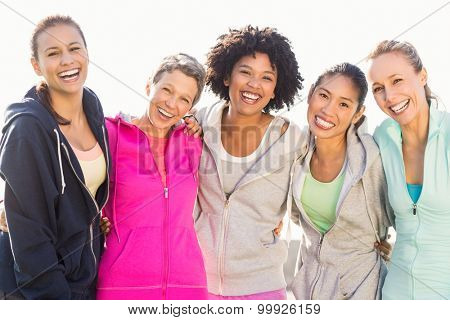 Portrait of laughing sporty women with arms around each other in parkland