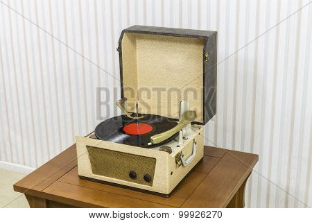 Vintage record player with vinyl album on wood table.