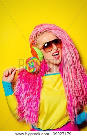 Attractive glamorous girl wearing ultra bright clothes and with pink dreadlocks eating lollipop. Bright style. Party style.