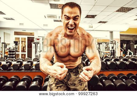 Expressive athletic man working out with dumbbells in a gym.