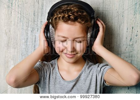 Cool teen girl enjoys the music in headphones. Studio shot.
