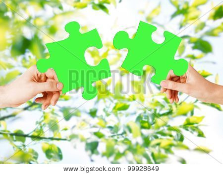 nature, ecology, energy saving, people and environment concept - close up of couple hands trying to connect green puzzle pieces over natural background