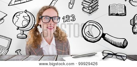 smiling geeky hipster girl looking at something against desk