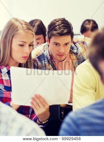 education, high school, teamwork and people concept - group of students with papers or test on exam
