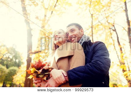 love, relationship, family and people concept - smiling couple with bunch of leaves hugging in autumn park