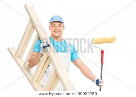 Young house painter holding a paint roller and a wooden ladder isolated on white background