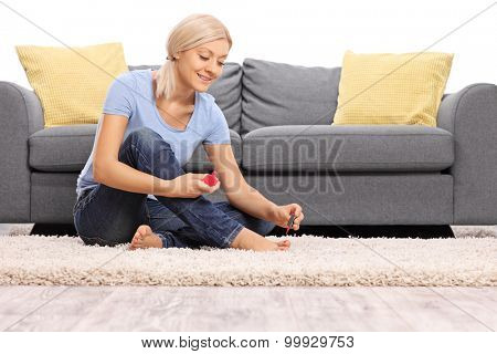 Young woman polishing her toenails seated on the floor in front of a gray sofa isolated on white background