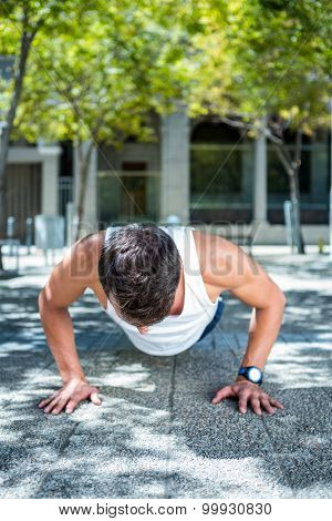 Handsome athlete doing push ups in the city