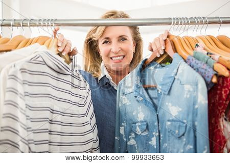 Portrait of smiling woman looking through the clothes rail in clothing store