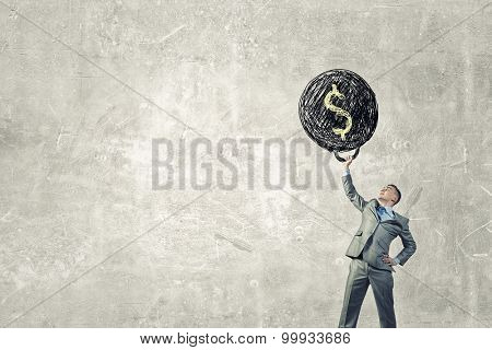 Young businessman lifts up heavy weight with dollar sign