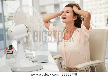 Casual businesswoman being cooled by ventilator in the office