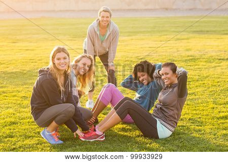 Portrait of smiling sporty women doing sit ups during fitness class in parkland