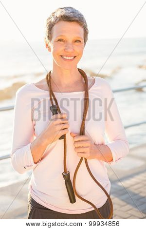Portrait of smiling sporty woman with skipping rope at promenade