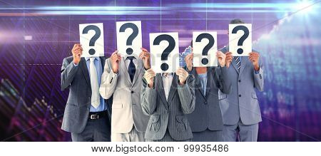 Business colleagues hiding their face with question mark sign against stocks and shares