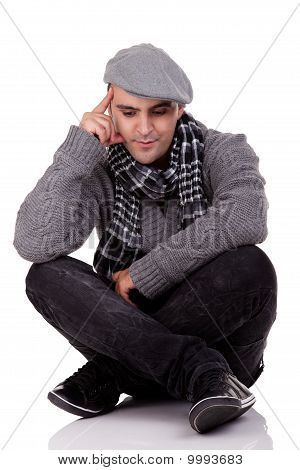Portrait Of A Young Man Sitting On The Floor, Thinking And Looking Down, In Autumn/winter Clothes, I